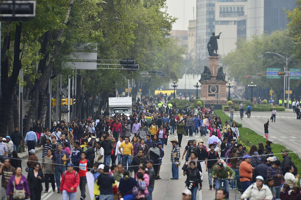 People walk to their jobs along Reforma Avenue as teachers hold roadblocks in the surroundings of the chamber of senators, in Mexico City on September 3, 2013. The Mexican goverment is facing the third week of protest by teachers who are against an education reform legislation. President Enrique Pena Nieto pushed through Congress changes to the constitution in December in order to put education, which was in the hands of powerful unions, back under government control and require teachers to undergo mandatory performance appraisals. AFP PHOTO/ Yuri CORTEZ